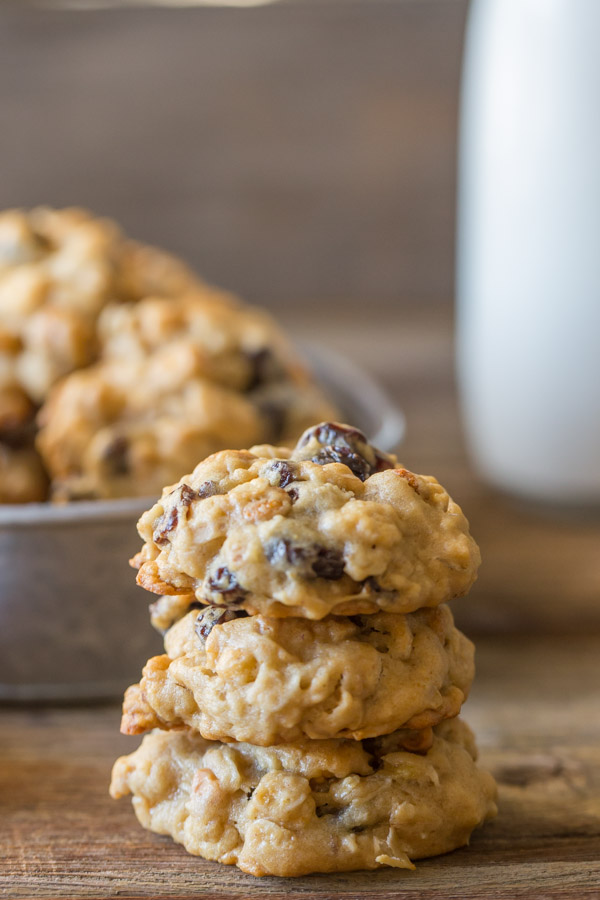 Healthy Breakfast Cookies stacked in a pile of three, with more cookies and milk in the background.