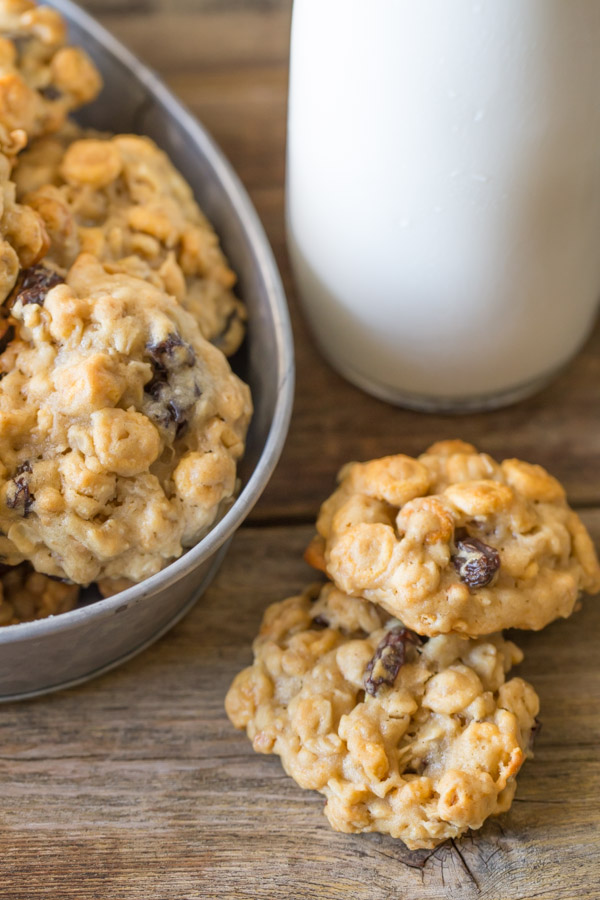 Two Healthy Breakfast Cookies sitting next to a galvanized metal bowl full of cookies and a glass of milk.