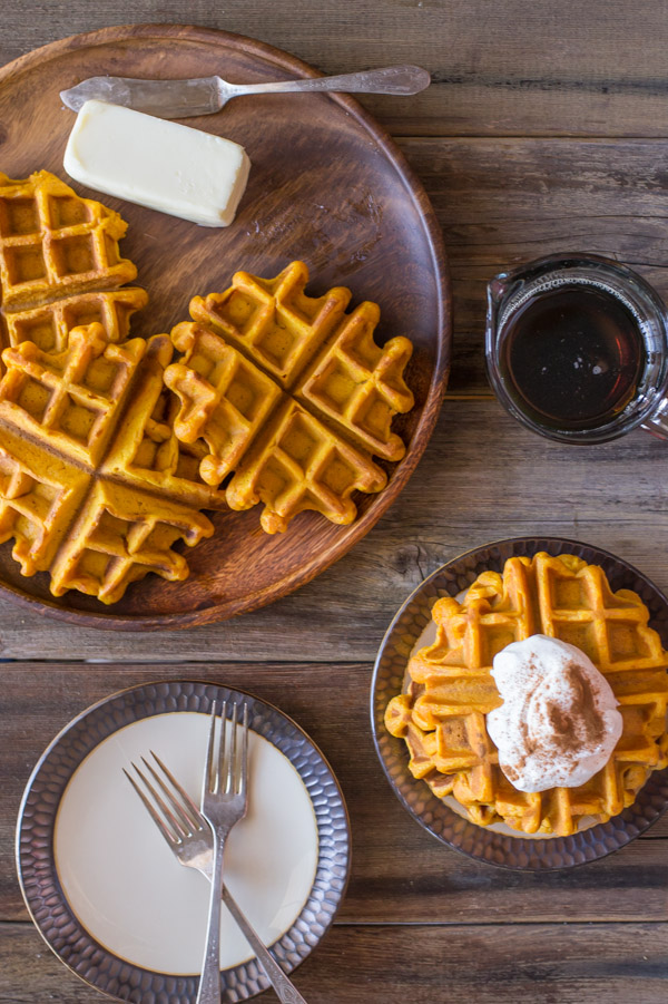 Pumpkin Spice Waffles on a wood serving plate with butter and a butter knife, sitting next to a glass container of maple syrup, a plate with a stack of Pumpkin Spice Waffles topped with whipped cream and cinnamon, and a plate with two forks on it.