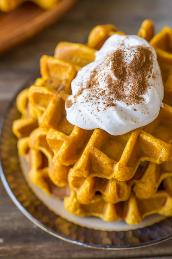 Pumpkin Spice Waffles stacked on a plate, topped with whipped cream and cinnamon.