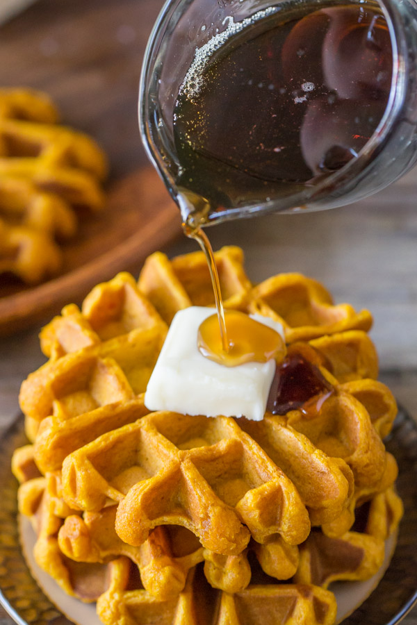 Pumpkin Spice Waffles stacked on a plate and topped with butter, with maple syrup being poured on top.