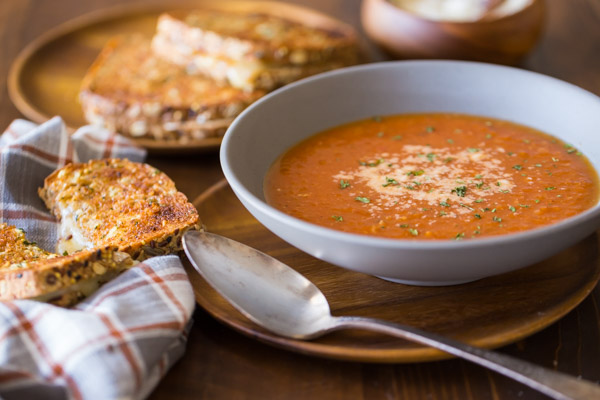 Homemade Tomato Soup in a bowl topped with grated Parmesan cheese, with a Garlic Bread Toasted Cheese Sandwich next to it and more sandwiches on a wood plate in the background.