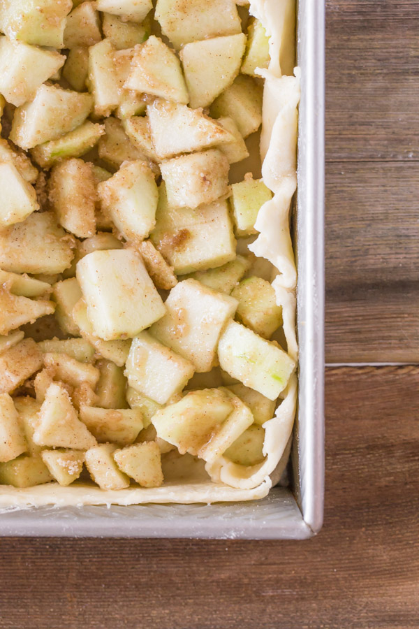 A baking pan with the bottom pie dough and apple mixture in it for the Iced Apple Pie Bars.