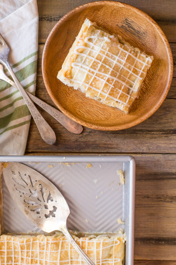 An Iced Apple Pie Bar on a wood plate, sitting next to the baking dish of Iced Apple Pie Bars with a serving spatula in it.