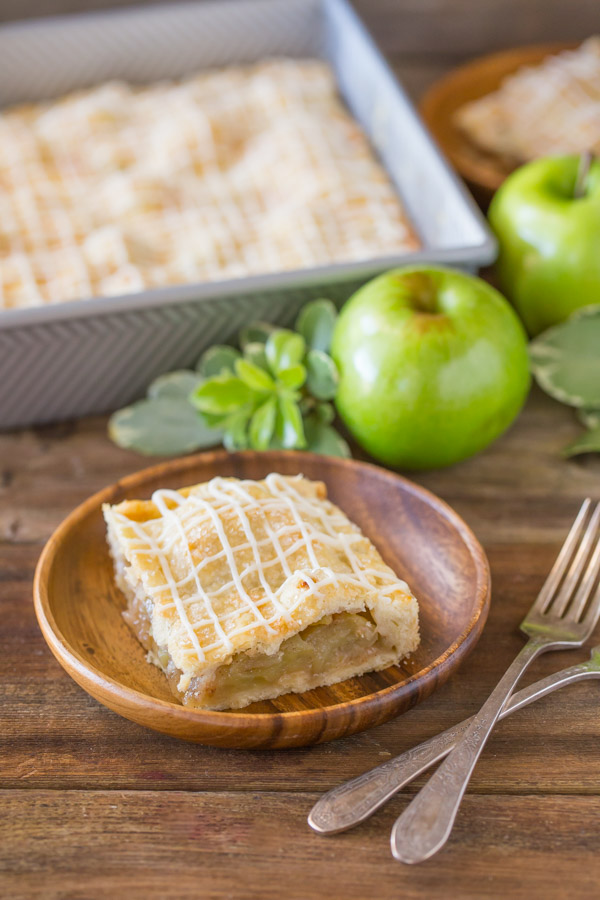 An Iced Apple Pie Bar on a wood plate, with the pan of Iced Apple Pie Bars in the background with some whole apples.