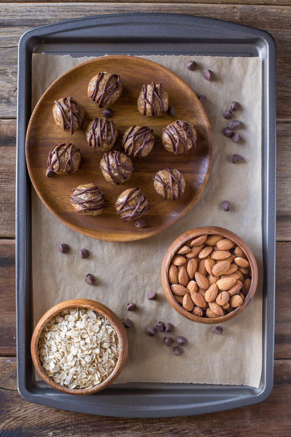 No Bake Energy Bites on a wood plate, drizzled with melted chocolate, sitting next to a bowl of almonds and a bowl of oats.