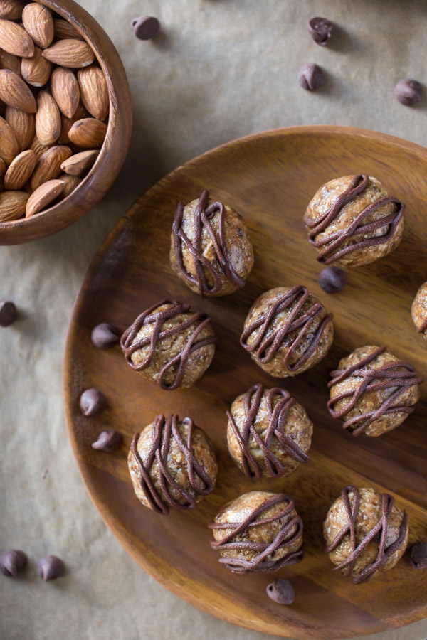 No Bake Energy Bites on a wood plate, drizzled with melted chocolate, sitting next to a bowl of almonds.