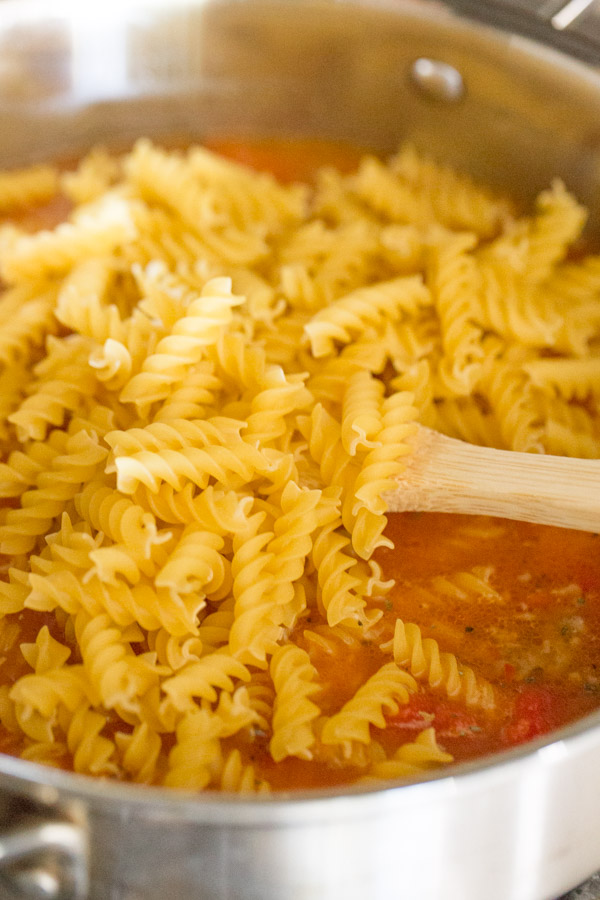 A large pan with all the ingredients for the One Pot Fusilli With Tomato, Basil, and Mozzarella in it.