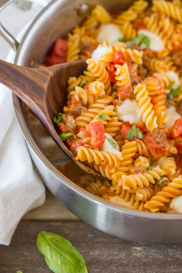 One Pot Fusilli With Tomato, Basil, and Mozzarella in a large pan with a wood serving spoon.