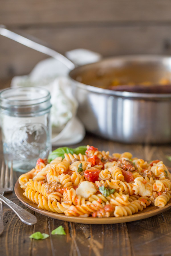 One Pot Fusilli With Tomato, Basil, and Mozzarella served on a wood plate, with a glass of water and the large pan of pasta in the background.
