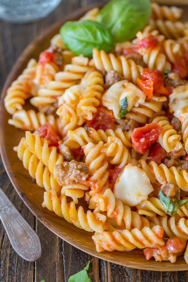One Pot Fusilli With Tomato, Basil, and Mozzarella on a wood plate.
