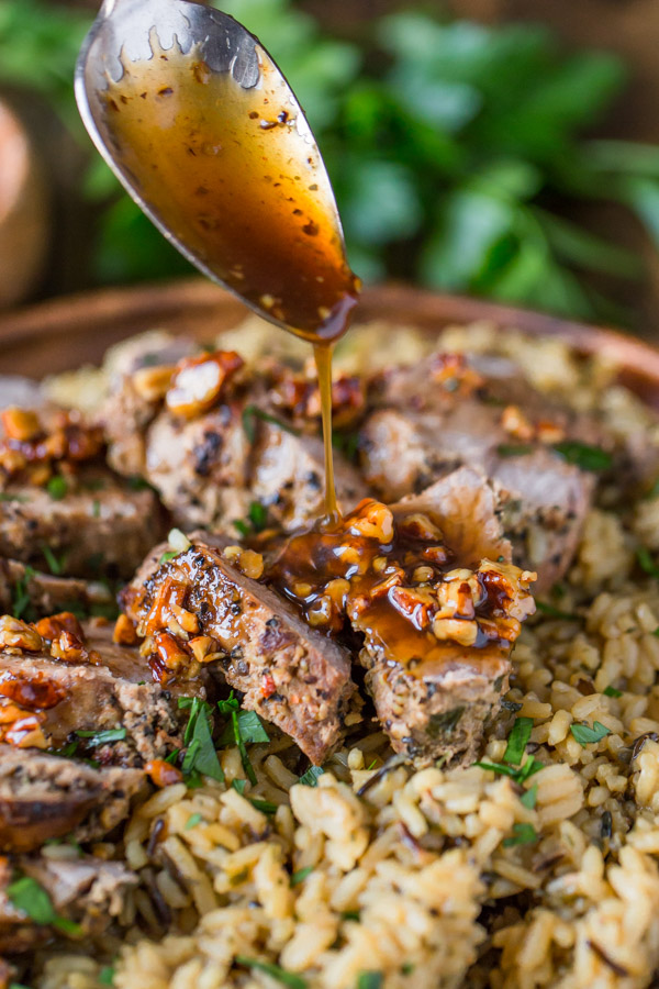 Pork Tenderloin sliced and served over rice with some Sweet Chili Pecan Glaze being spooned over the top.