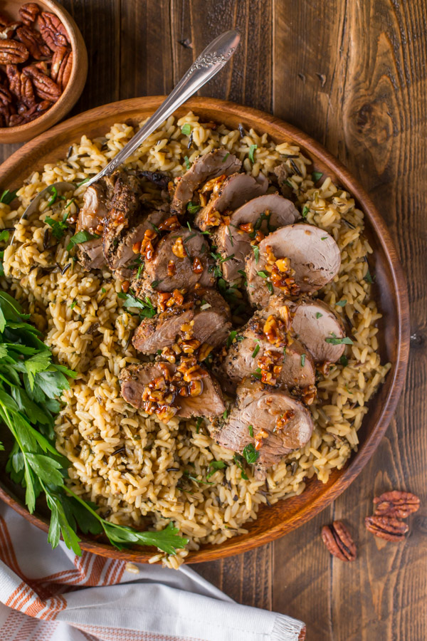 Pork Tenderloin sliced and served over rice and topped with a Sweet Chili Pecan Glaze on a wood plate with a serving spoon in it, with a small wood bowl of pecans next to it.