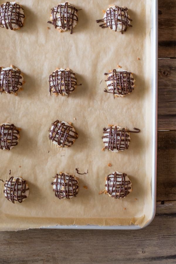 Stuffed Chocolate Almond Macaroons that have been drizzled with chocolate, sitting on a parchment paper lined baking sheet.