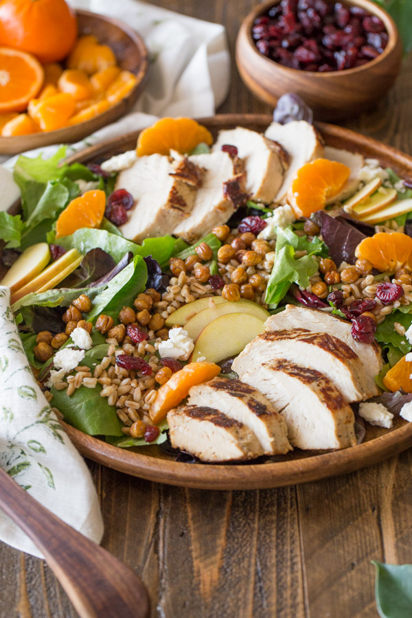 Turkey Farro Salad With Candied Chickpeas on a wood serving plate, with a wood plate of clementines and a wood bowl of dried cranberries in the background.