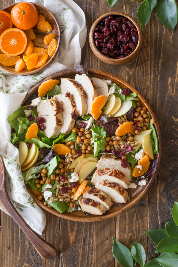 Turkey Farro Salad With Candied Chickpeas on a wood serving plate, with a wood plate of clementines and a wood bowl of dried cranberries next to it.