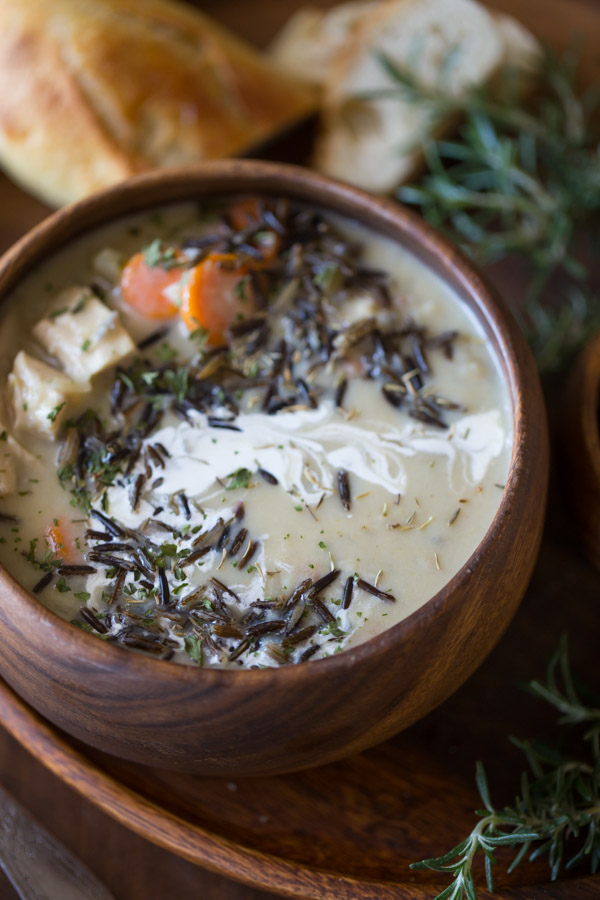 Creamy Chicken and Wild Rice Soup in a wood bowl, sitting on a wood plate along with some bread.