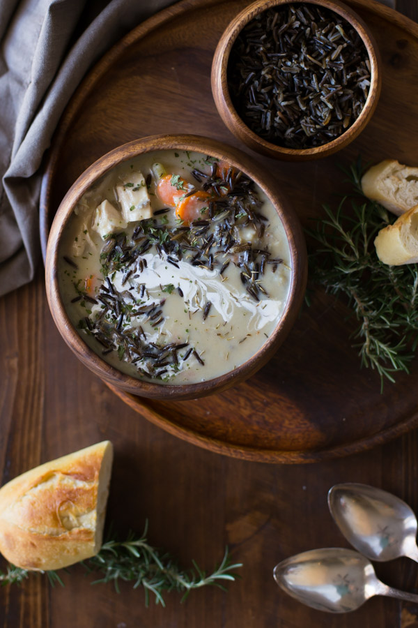 Creamy Chicken and Wild Rice Soup in a wood bowl, sitting on a wood plate along with a small wood bowl of wild rice and some bread, with two spoons and more bread sitting next to the plate.
