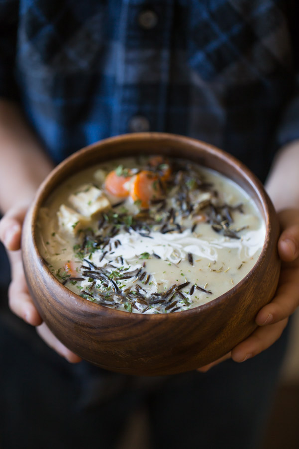 Creamy Chicken and Wild Rice Soup in a wood bowl, being held by a child.