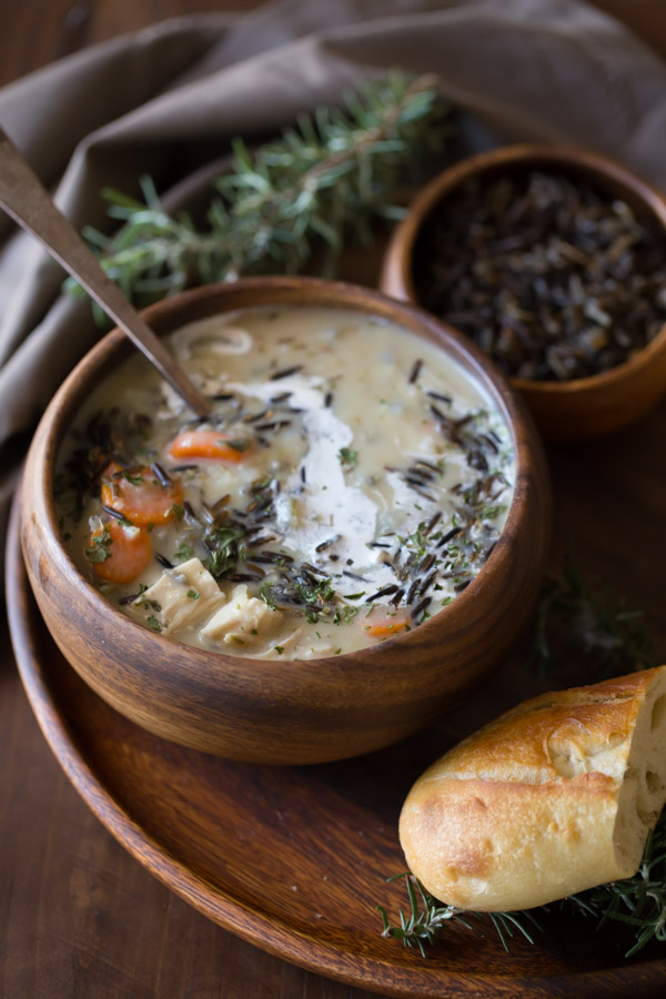 Creamy Chicken and Wild Rice Soup in a wood bowl, sitting on a wood plate along with a small wood bowl of wild rice and a piece of bread.