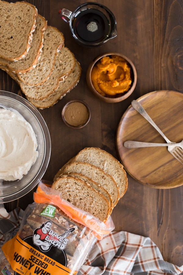 Pumpkin Pie Spiced Stuffed French Toast ingredients - a small wood bowl of pumpkin spice, a small wood bowl of pumpkin puree,  a glass pour cup of maple syrup, slices of bread, a glass bowl of the cream cheese filling - sitting next to a plate with two forks.