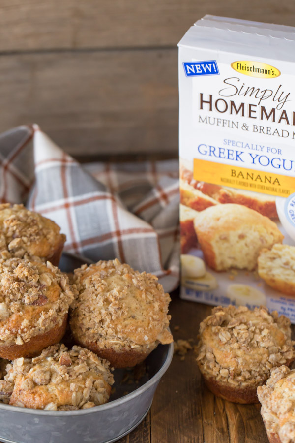 Banana Muffins With Almond Oat Streusel Topping in a galvanized bowl, sitting next to a box of Fleischmann's Simply Homemade Muffin & Bread Mix, banana flavor and two more muffins.