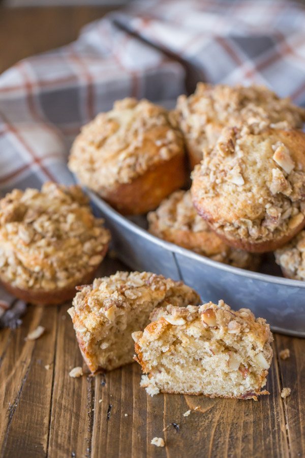 A Banana Muffin With Almond Oat Streusel Topping cut in half, with a galvanized bowl of muffins in the background.