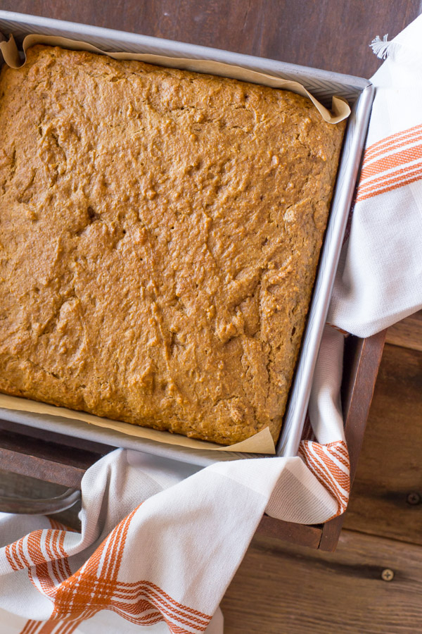 Healthier Pumpkin Spice Snack Cake in a parchment paper lined baking pan.
