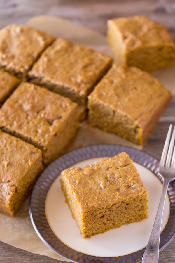 Healthier Pumpkin Spice Snack Cake cut into square pieces, with one piece on a plate with a fork.