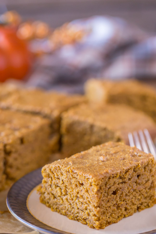 A piece of Healthier Pumpkin Spice Snack Cake on a plate, with more of the cake in the background.