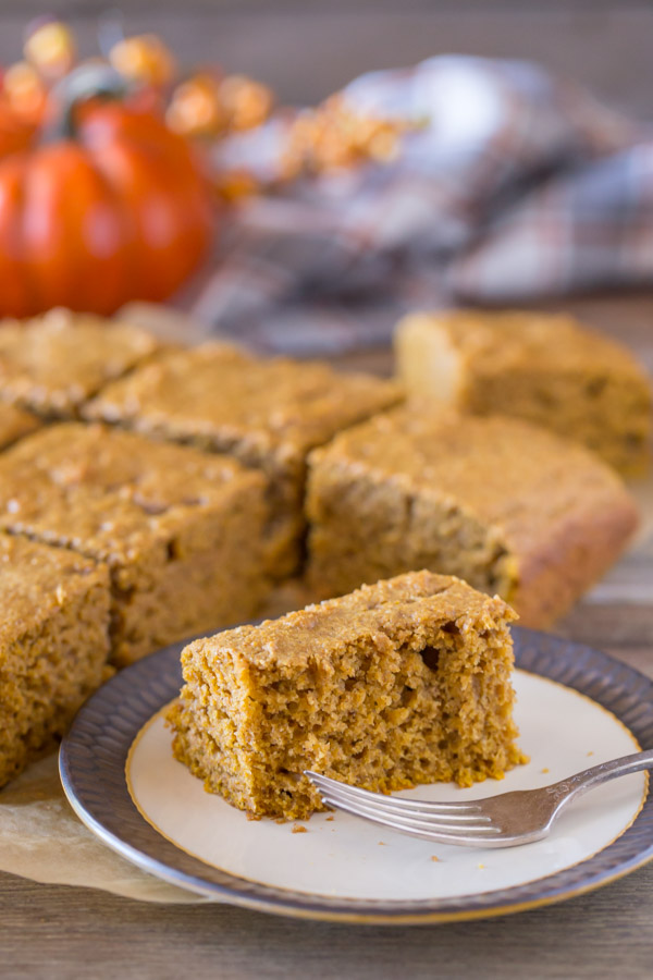 A half eaten piece of Healthier Pumpkin Spice Snack Cake on a plate with a fork, with the rest of the cut cake in the the background.