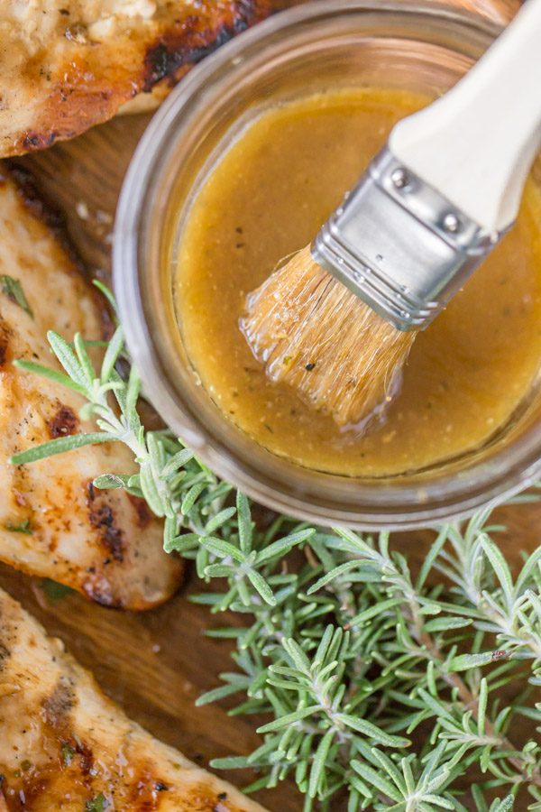 A glass jar of the Honey Mustard Sauce with a basting brush in it, sitting next to some Grilled Chicken and fresh rosemary.
