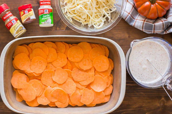 A baking dish with the sweet potato slices in it, sitting next to a glass cup of the heavy cream mixture, a bowl of shredded cheese and some spices.