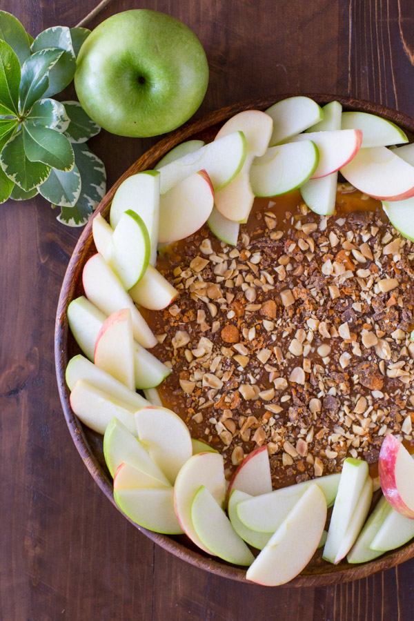 Easy Caramel Apple Dip on a wood plate with sliced apples arranged around it, and a whole apple sitting next to it.