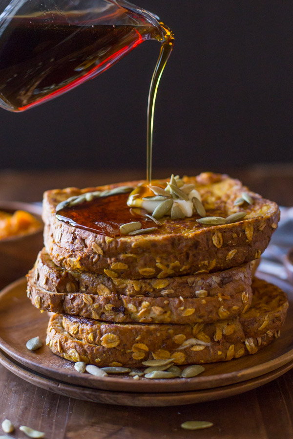 Pumpkin Pie Spiced Stuffed French Toast stacked on a wood plate, topped with butter and pepitas, with maple syrup being poured on top.