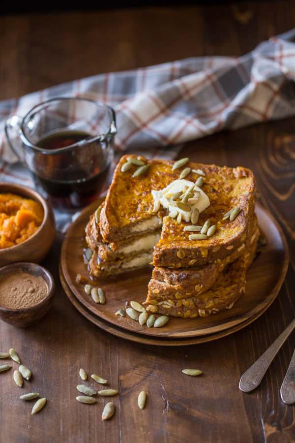 Pumpkin Pie Spiced Stuffed French Toast stacked on a wood plate and topped with butter, pepitas and maple syrup, with a section of the stack cut out.  A small wood bowl of pumpkin spice, a small wood bowl of pumpkin puree, and a glass pour cup of maple syrup are sitting next to the plate.