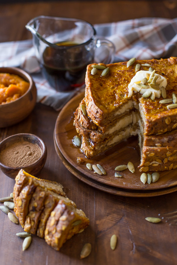 Pumpkin Pie Spiced Stuffed French Toast stacked on a wood plate and topped with butter, pepitas and maple syrup, with a section of the stack cut out and laying next to the plate, along with a small wood bowl of pumpkin spice, a small wood bowl of pumpkin puree, and a glass pour cup of maple syrup.