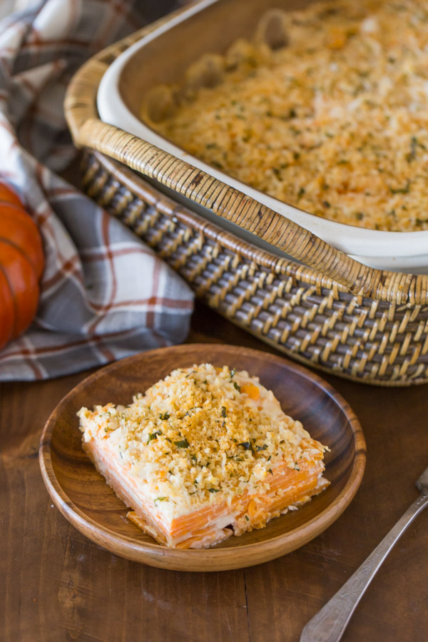 A serving of Smoked Chili Sweet Potato Gratin on a wood plate, with the baking dish of Smoked Chili Sweet Potato Gratin in the background.