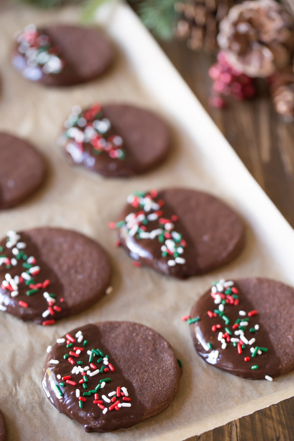 Chocolate Cut-Out Cookies that have been half dipped in melted chocolate and covered with sprinkles.