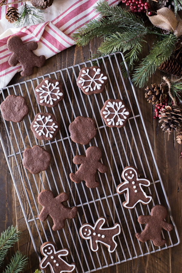 A cooling rack with Snowflake and Gingerbread Men Chocolate Cut-Out Cookies, with some decorated with icing.