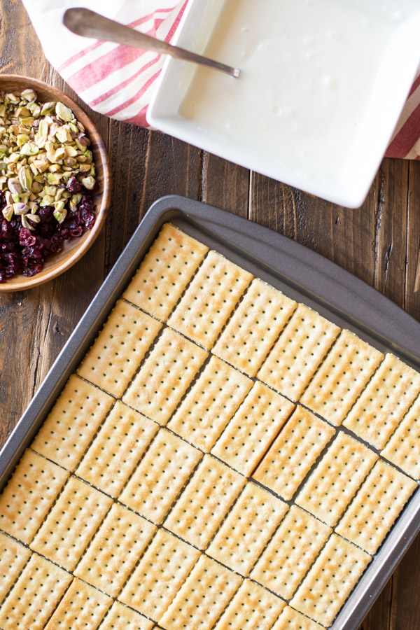 Butter crackers arranged on a baking sheet, sitting next to a wood bowl of chopped cranberries and pistachios, and a bowl of melted white chocolate.