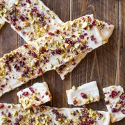 Cranberry Pistachio Butter Cracker Bark - A thin layer of white chocolate on a flaky buttery cracker with a sprinkle of dried cranberries and pistachios.