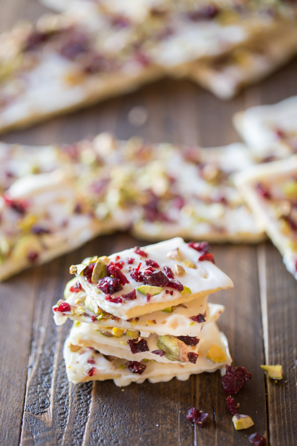 A few pieces of Cranberry Pistachio Butter Cracker Bark stacked, with more Cranberry Pistachio Butter Cracker Bark in the background.