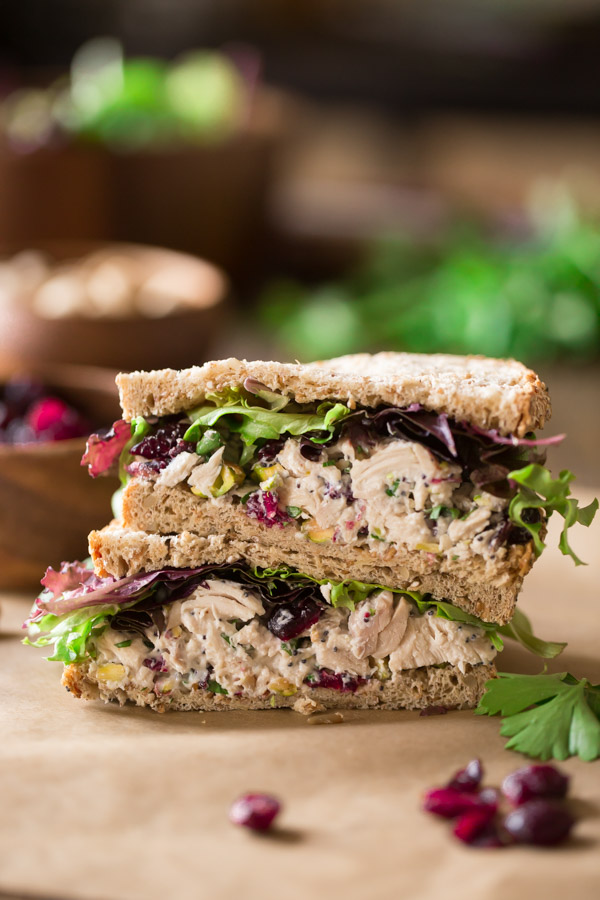 A Cranberry Pistachio Chicken Salad Sandwich cut in half and stacked on top of each other.