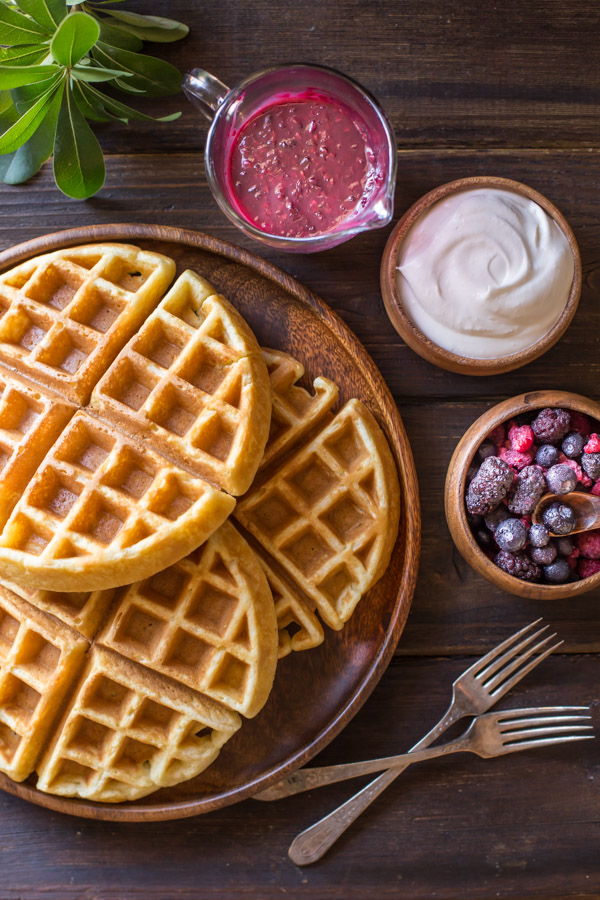 Best Ever Buttermilk Waffles stacked on a large wood plate, with a pour cup of berry sauce, a small bowl of whipped cream, a small bowl of mixed berries and two forks next to the plate.