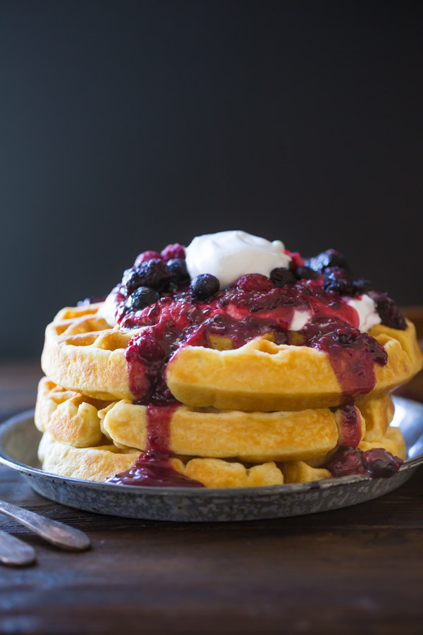Best Ever Buttermilk Waffles stacked on a plate, topped with berry sauce, whole berries and whipped cream.
