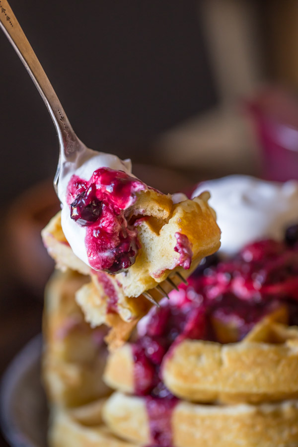 A fork full of the Best Ever Buttermilk Waffles topped with berry sauce, whole berries and whipped cream.