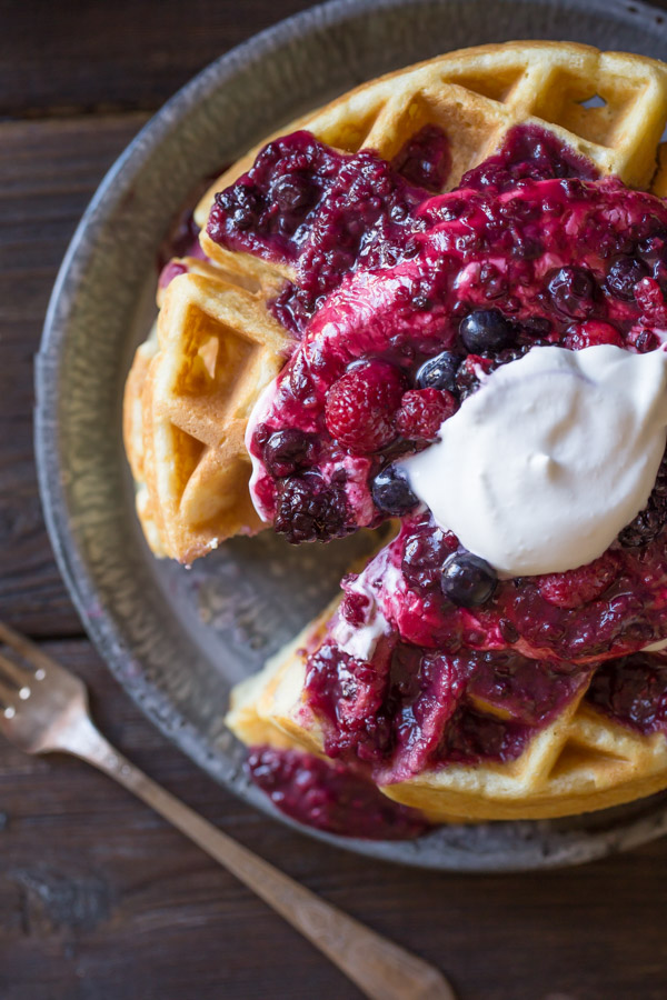 Best Ever Buttermilk Waffles on a plate, topped with berry sauce, whole berries and whipped cream.