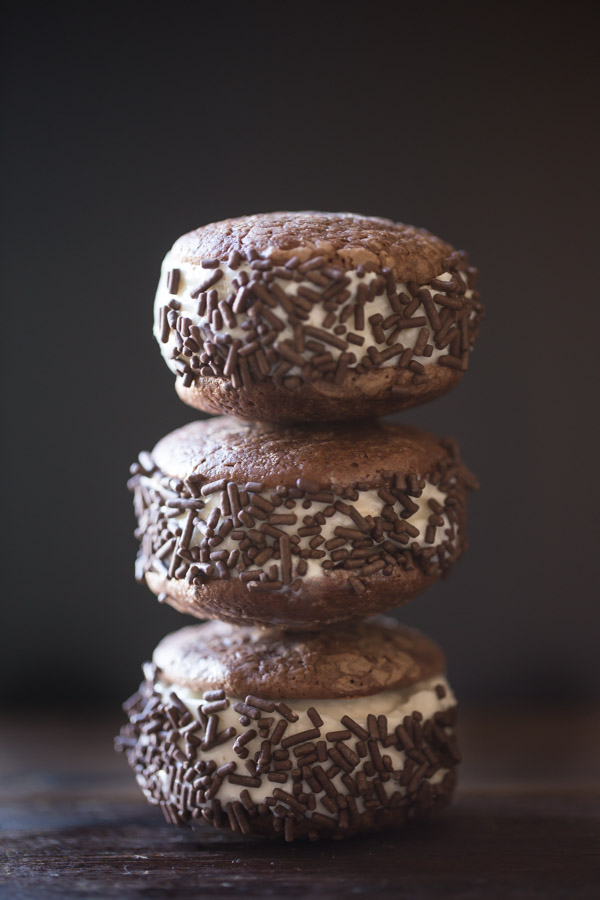 Three Brownie Cookie Ice Cream Sandwiches with chocolate sprinkles stacked on top of each other.
