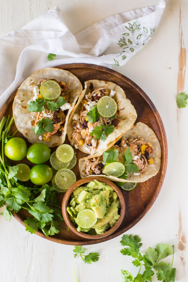 Three Crockpot Salsa Chicken Tacos arranged on a wood serving plate, with cilantro, limes and a small bowl of sliced avocado.